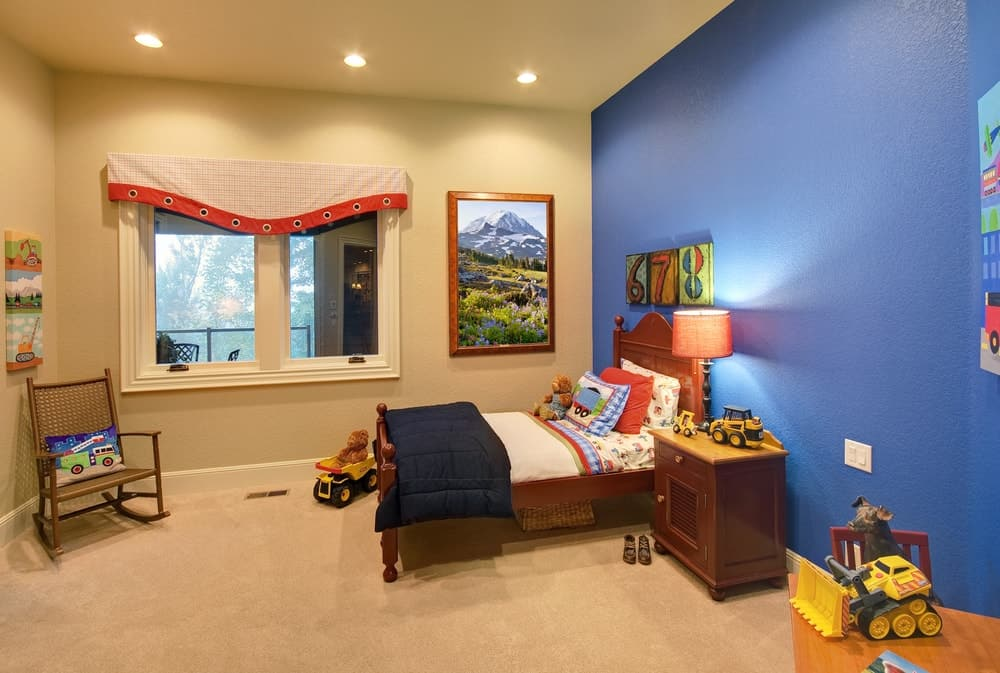 Kids bedroom with mix blue and cream walls along with carpet flooring and recessed lights.