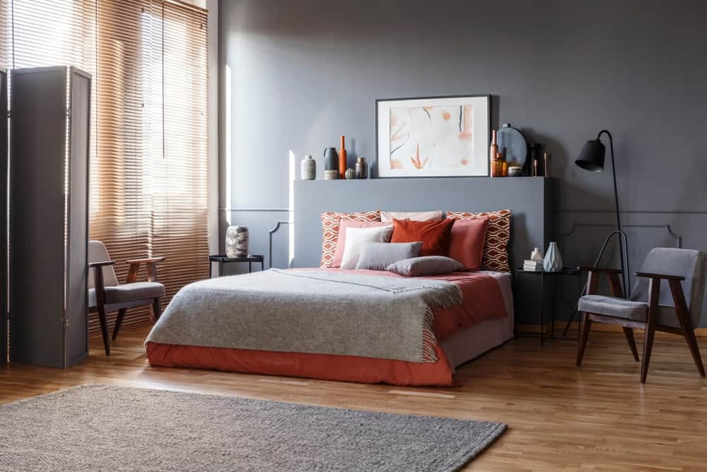 Bedroom with dark gray walls and laminated flooring along with a rug and floor lamp.