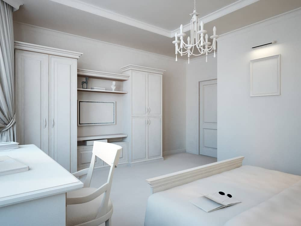 Pure white bedroom with a study desk and cabinet along with a chandelier.