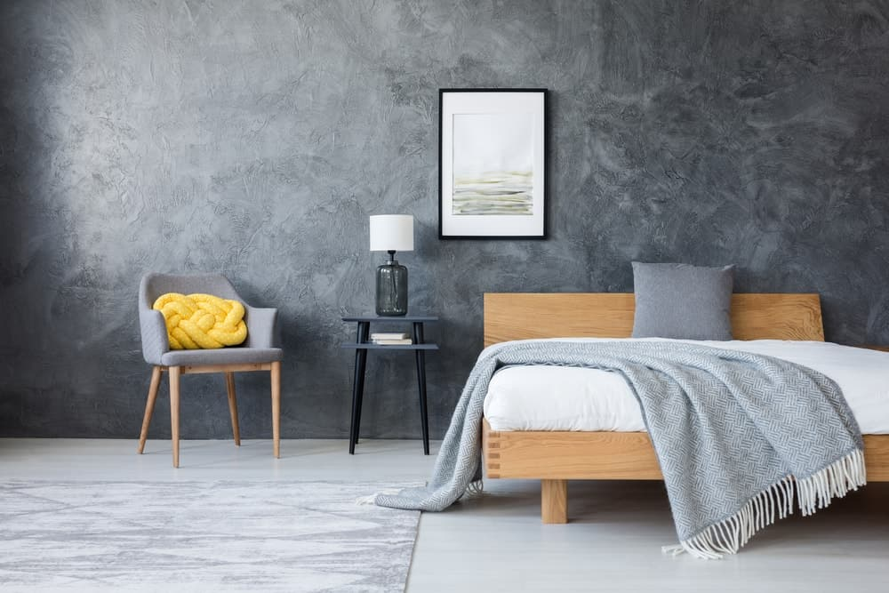Contemporary bedroom with stylish gray walls and smooth white floors along with a sitting area and a rug.
