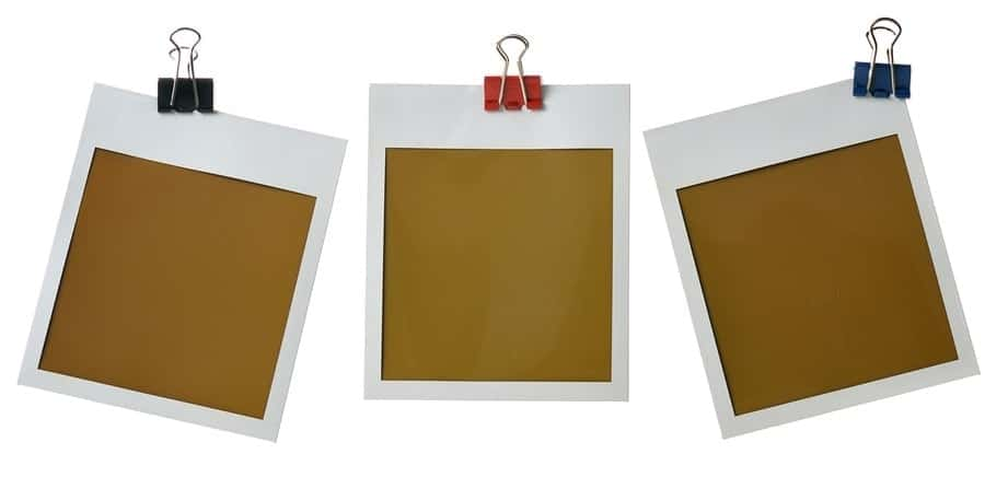 Empty photo frames attached to binder clips on white background.