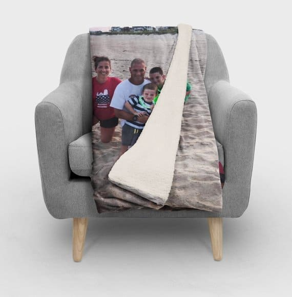 Family portrait printed on a sofa throw lying on a gray armchair.