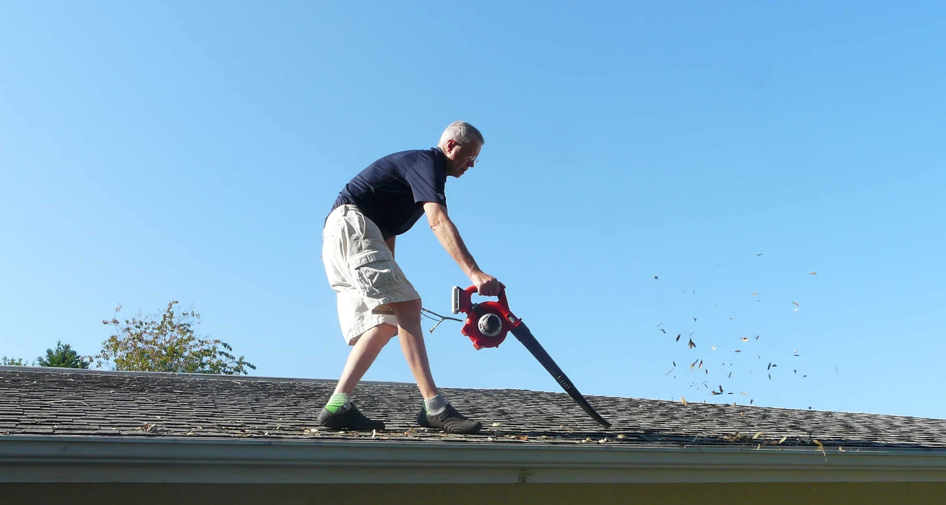 A man is on a roof and is using a blower to remove leaves and excess dirt from the gutter.