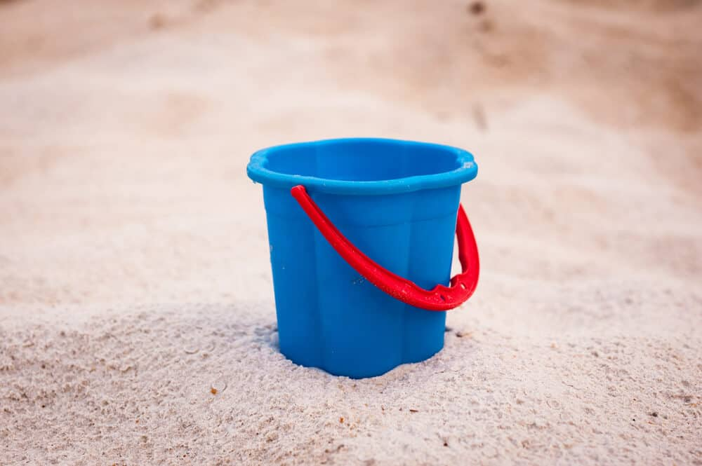 A blue, plastic bucket with a red handle.