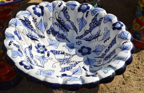 White, ceramic bird bath with blue Mexican-style details.