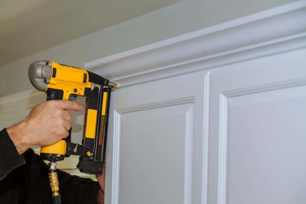 A worker is using a brad nailer to fix the door frame.