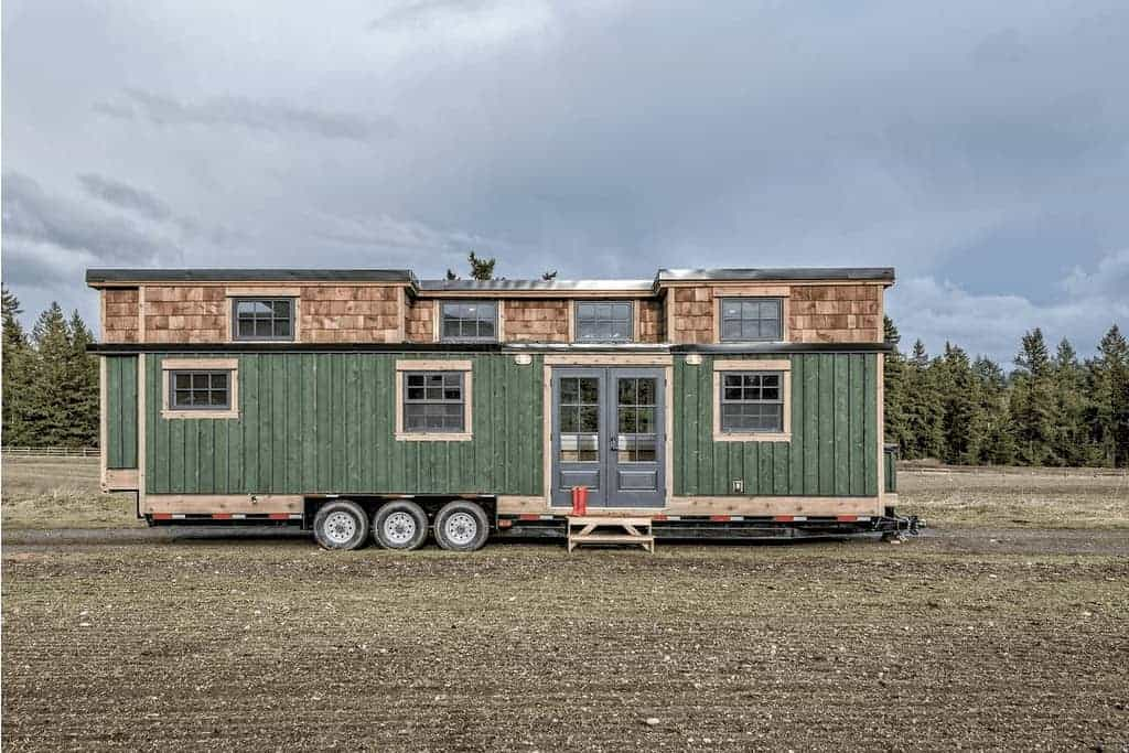 Green tiny house featuring 2 loft bedrooms and a breakfast bar.