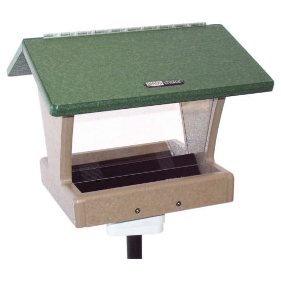 A bird feeder made of lumber having a green-colored roof and a natural brown foundation.