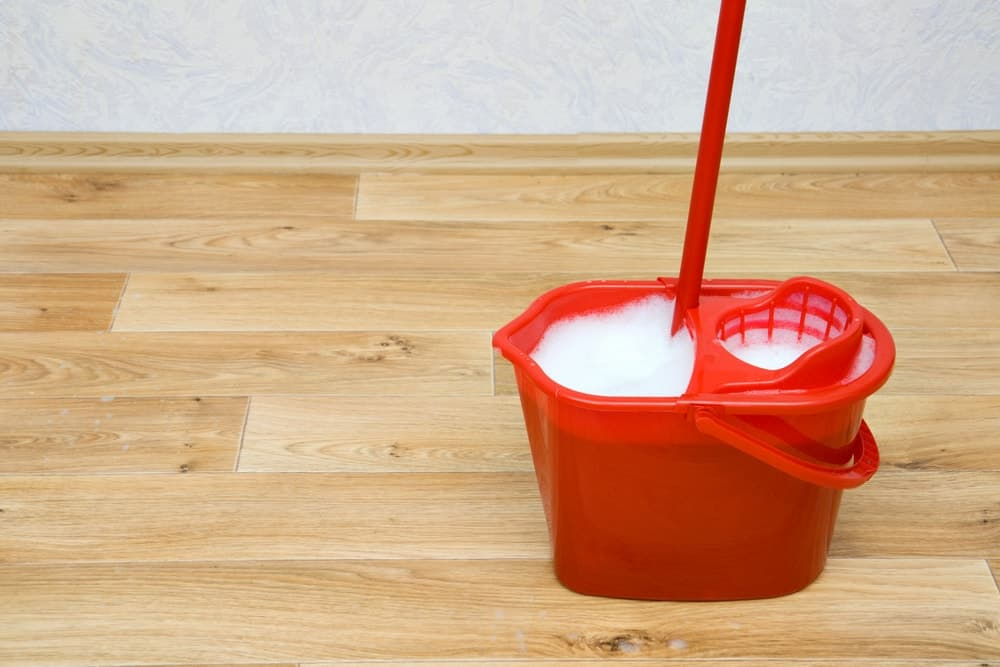 A red mop bucket with wringer filled with soapy water standing on wooden flooring.
