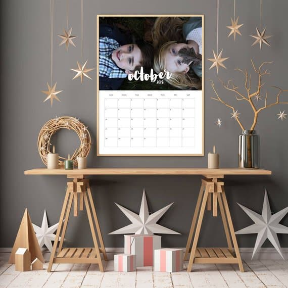 Personalized calendar displaying an enlarged photo of two kids for the month of October. Wooden desk and other home accessories surround the calendar.