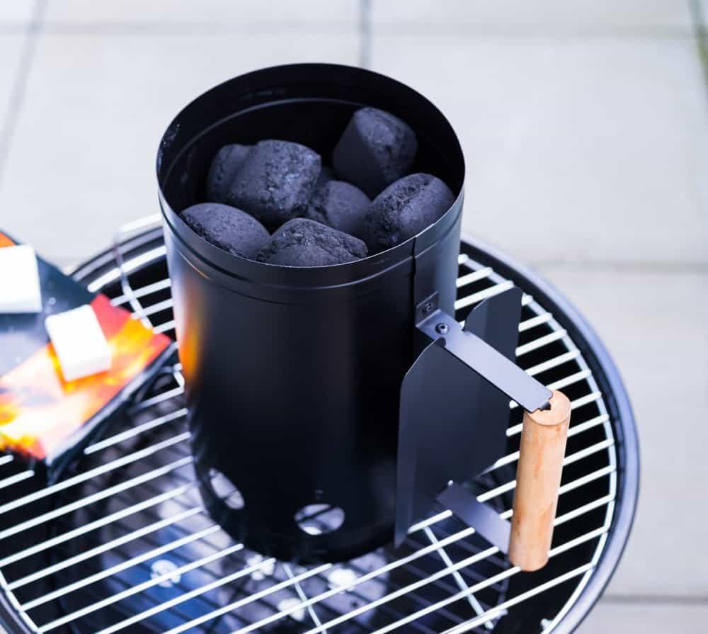Black chimney starter with wooden handle grip.