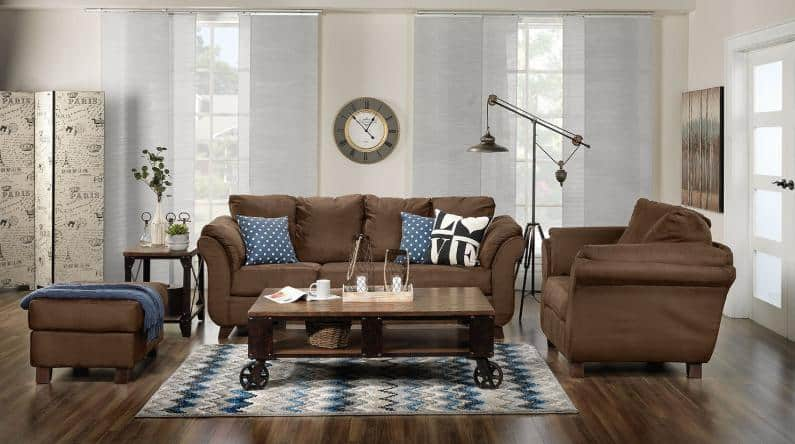 Chocolate brown sofa set with blue pillows.