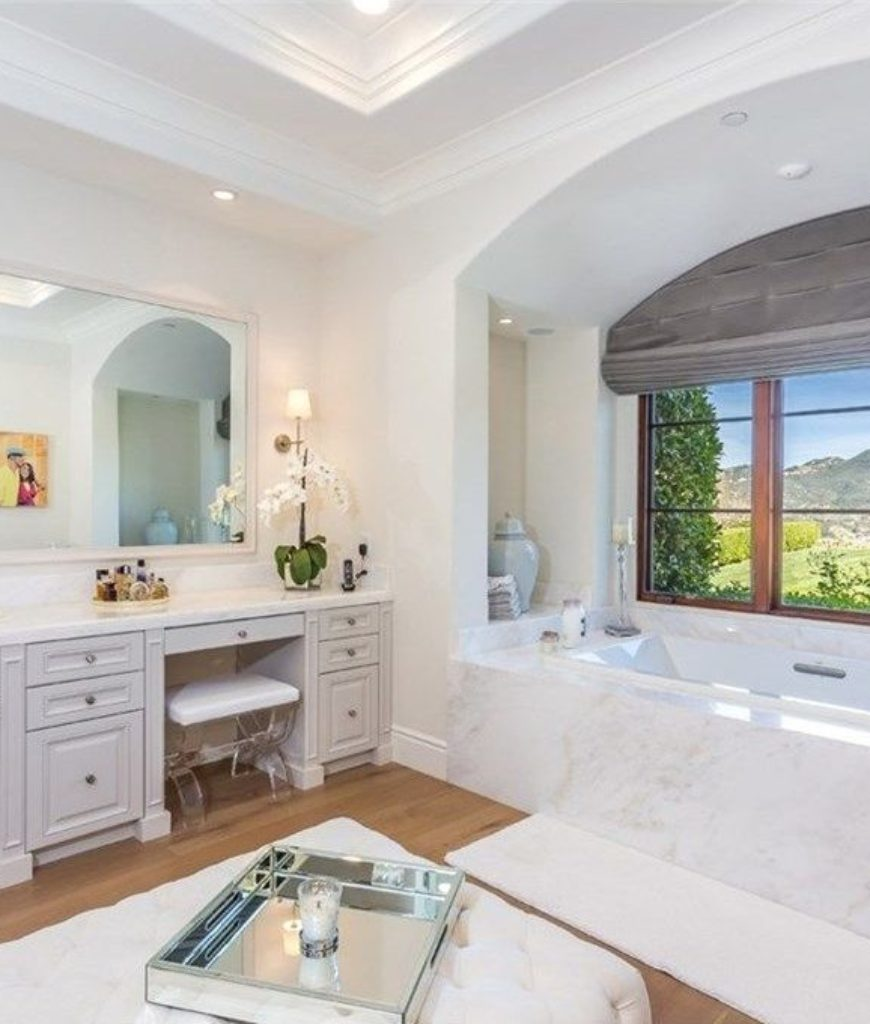 Another view of the bathroom featuring the corner bathtub near the window overlooking the beautiful outdoor area.