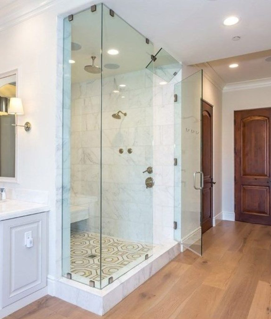 The bathroom has a complete shower and soaking tub along with a TV on wall.