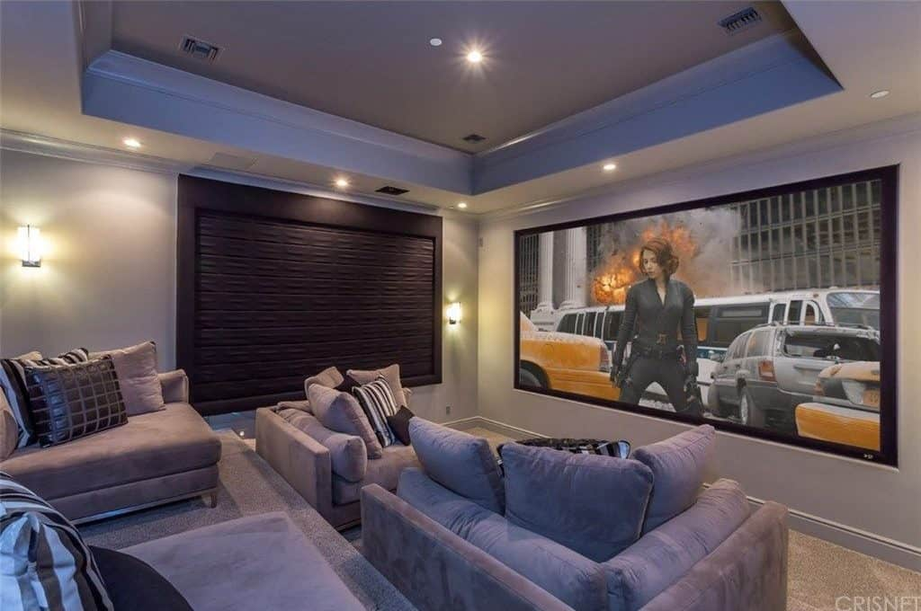 A Cozy Home Theater With Comfortable Sectional Sofa Seats Under The Stunning Tray Ceiling Lighted By