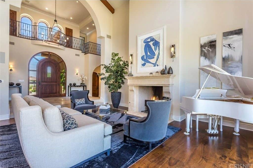 The formal living room features a white couch in front of a fireplace and has a white piano on the side.