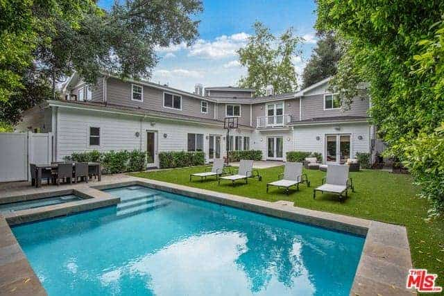 This home boasts a gray exterior along with a relaxing backyard with a well-maintained lawn area with multiple sitting lounges near the swimming pool.