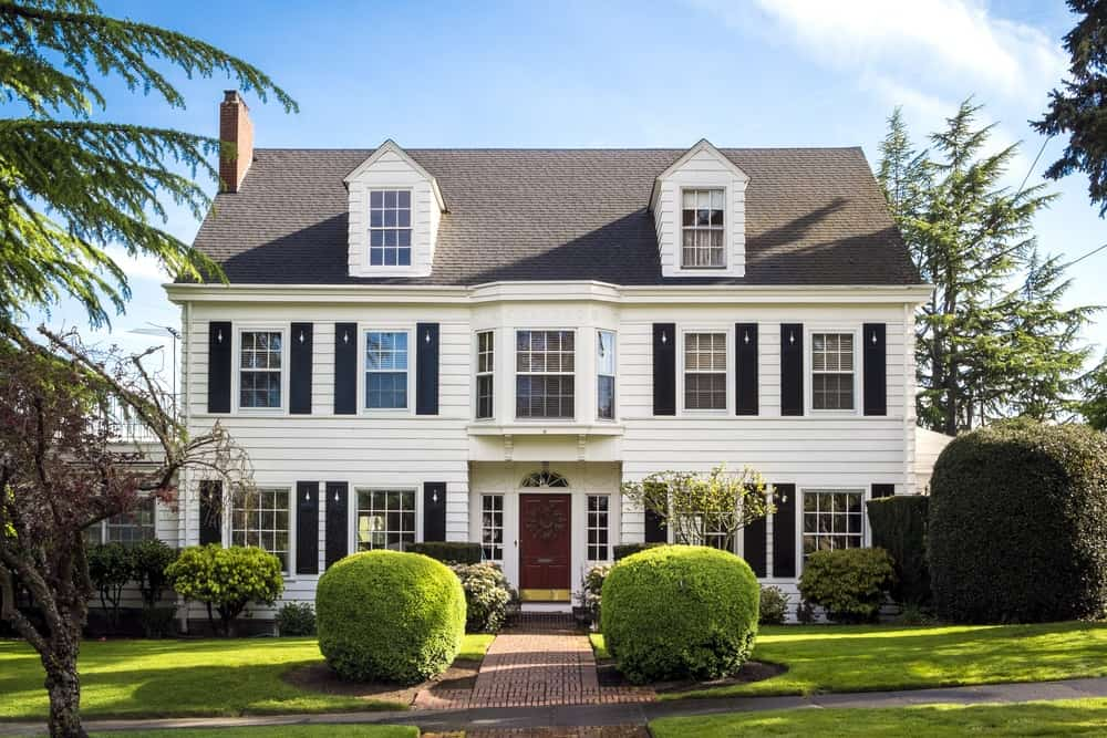 Classic suburban American house with sloping roof, two attics, and front porch and garden.