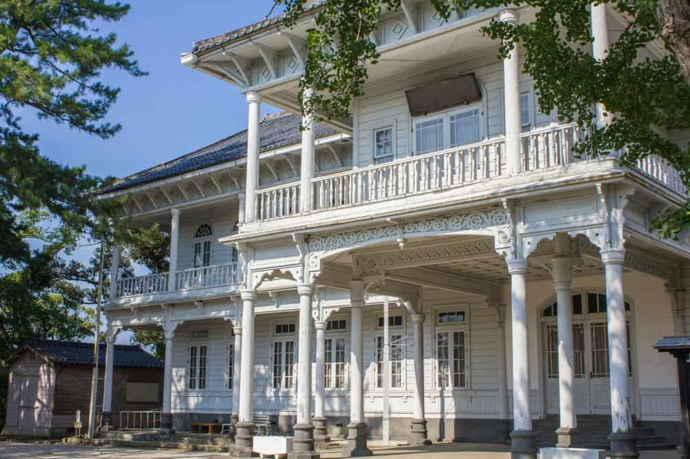 A classic, white, wooden nineteenth century mansion house with a long balcony stands