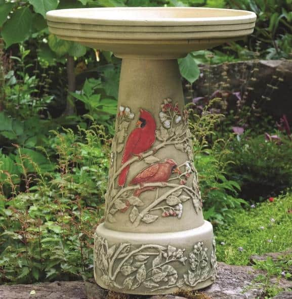 A clay bird bath with a decorated stand.