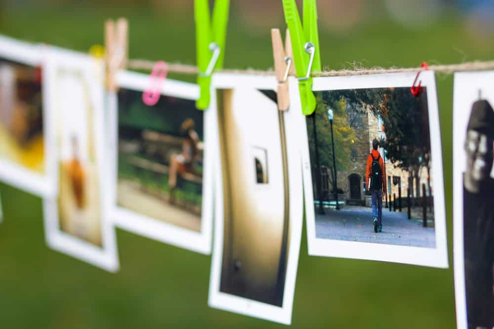 Polaroid photos hung on a clothesline outdoors.