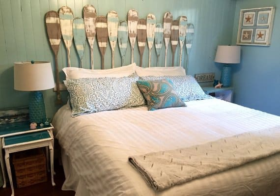 Small blue bedroom with distressed-looking canoe paddles as headboard, blue pillows on white bedding, and blue bedside lamps with white shades.