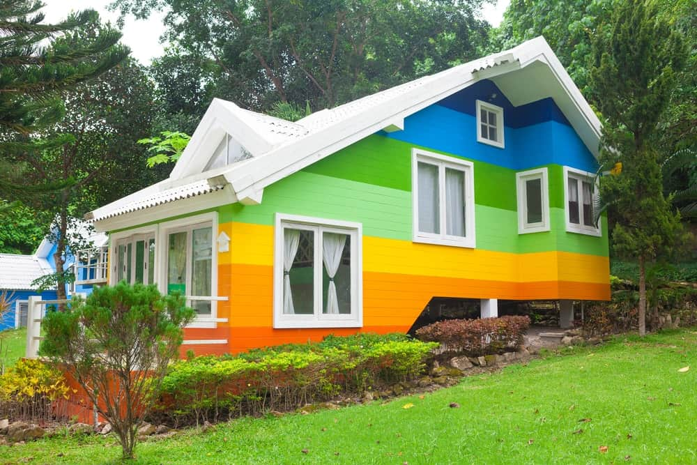 White trim is the perfect choice for letting all the bright colors of this rainbow-inspired house stand out. It also adds a crisp look to this whimsical house tucked in a green surround.
