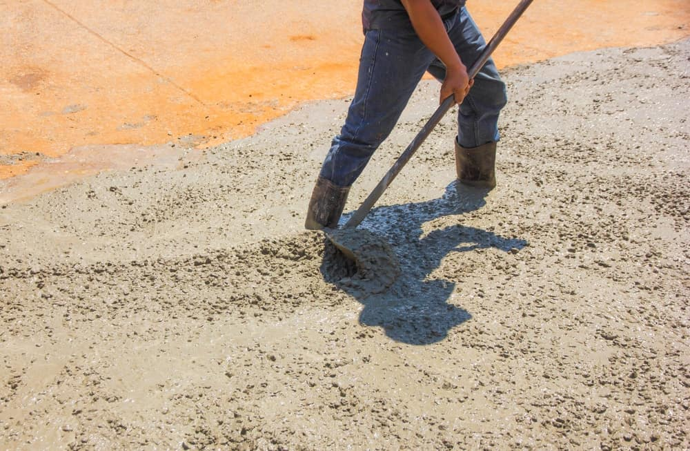 The come along rake is being used to properly distribute the cement over an applied surface.