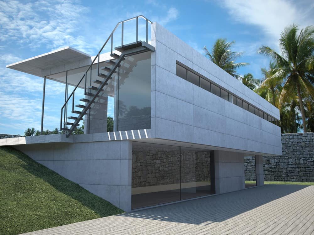 Concrete and glass home with rooftop balcony access to via steel stairs on the side of the house extending off the patio.
