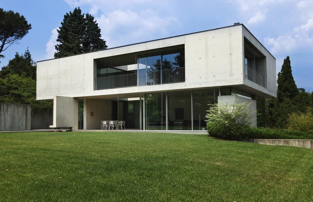 Modern two story concrete home where the upper floor is larger in footprint the bottom floor giving the home a table shape from the side.