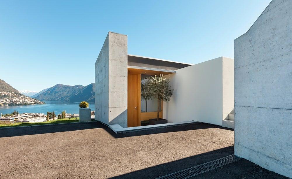 Hidden entrance to concrete exterior home overlooking the ocean.