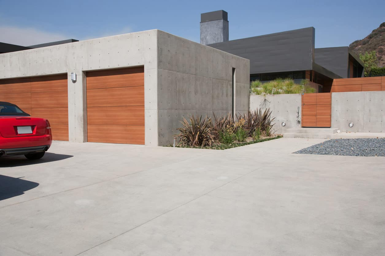 Front concrete exterior 3-car garage with wood garage doors forms the gated entrance to this large home. You access matching concrete fence.