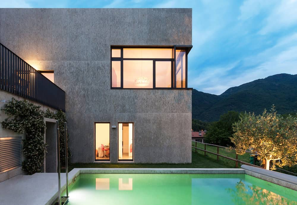 Square modern house with concrete exterior with great view of mountains and small backyard pool.