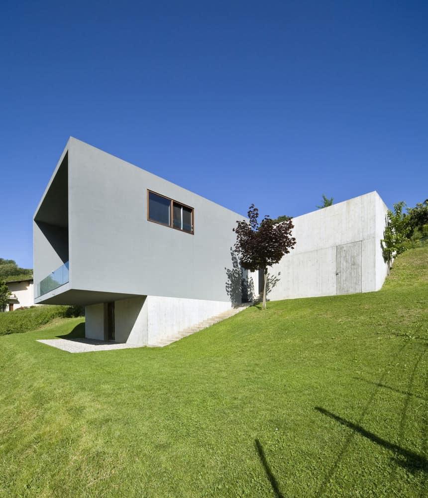 Bunker style concrete modern home built into grassy hillside.