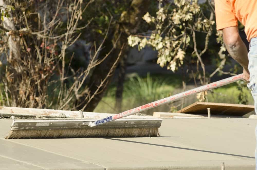 A worker is using the concrete finishing broom to even out the rough spots and remove the unwanted cement particles.