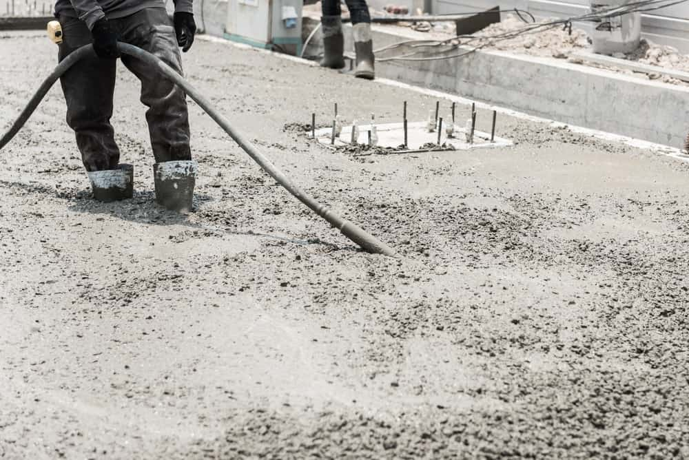 A construction worker is using the concrete vibrator to control the distribution of the cement on the surface.