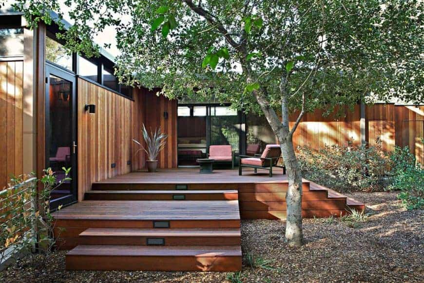 Contemporary mid-century style home with a wooden exterior and has a small deck with a sitting lounge.