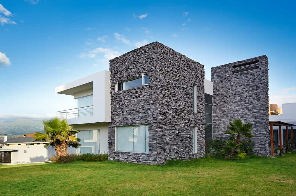 A modern house with one side made of painted concrete and the other side made of durable stone exteriors.