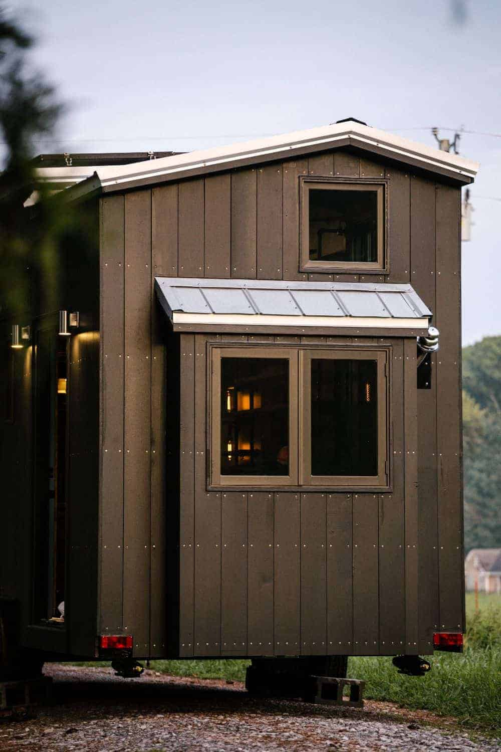 An industrial tiny wooden house with glass windows and wall lights.