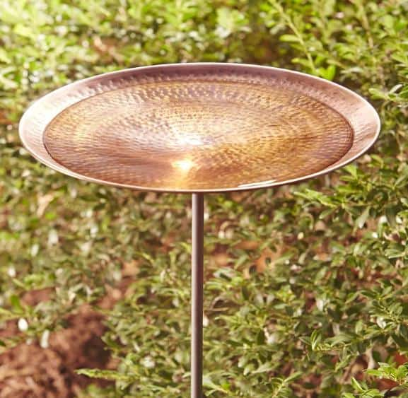 An antique, copper bird bath blends well with the outdoor tones.