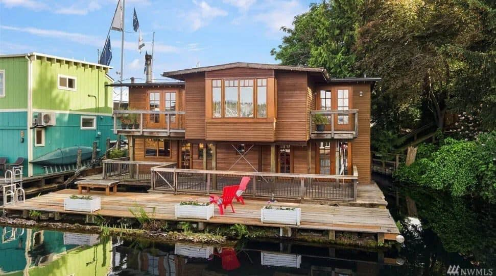 A wooden craftsman home floating on a floating wooden deck platform.