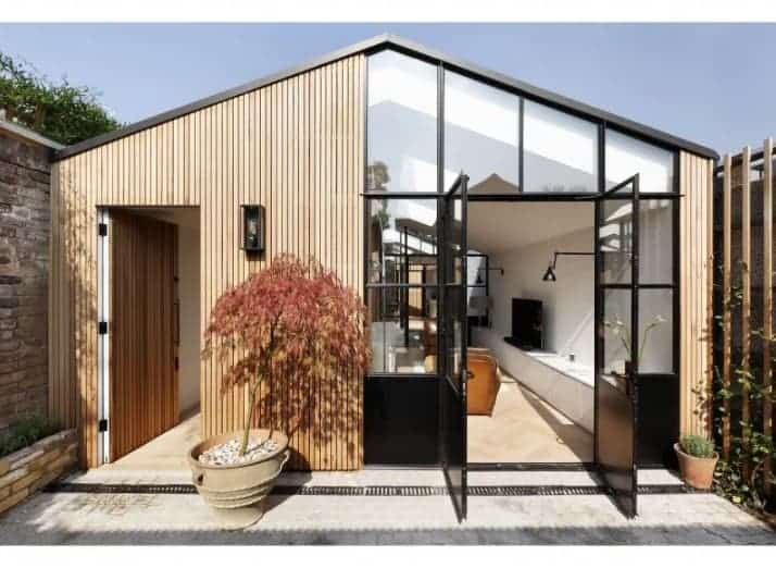 A modern house featuring a wooden exterior with glass windows and doors.