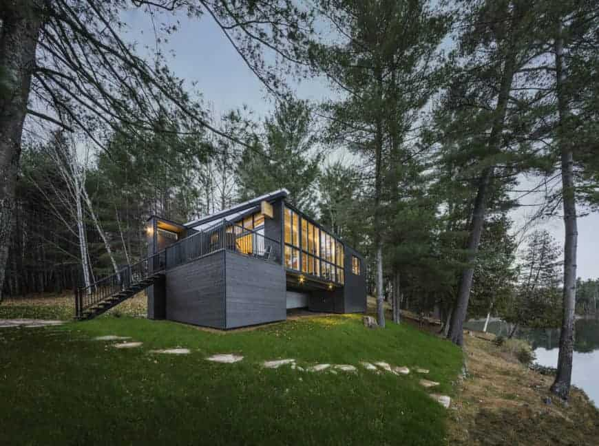 Cross-laminate timber cottage house with a gray exterior and a nice view of the lake.