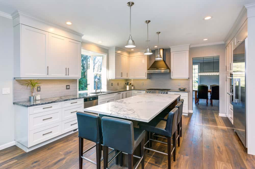 Stylish long new kitchen with white cabinets, dark countertops and then the island being the reverse - dark base with white top.