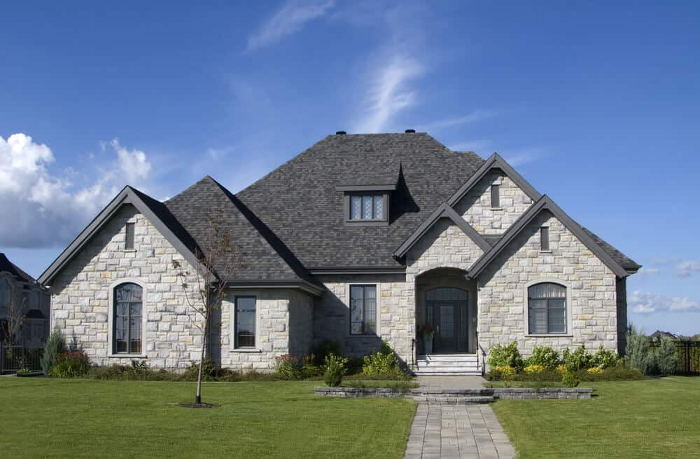A sturdy-looking luxury stone house in light and dark tones of gray.
