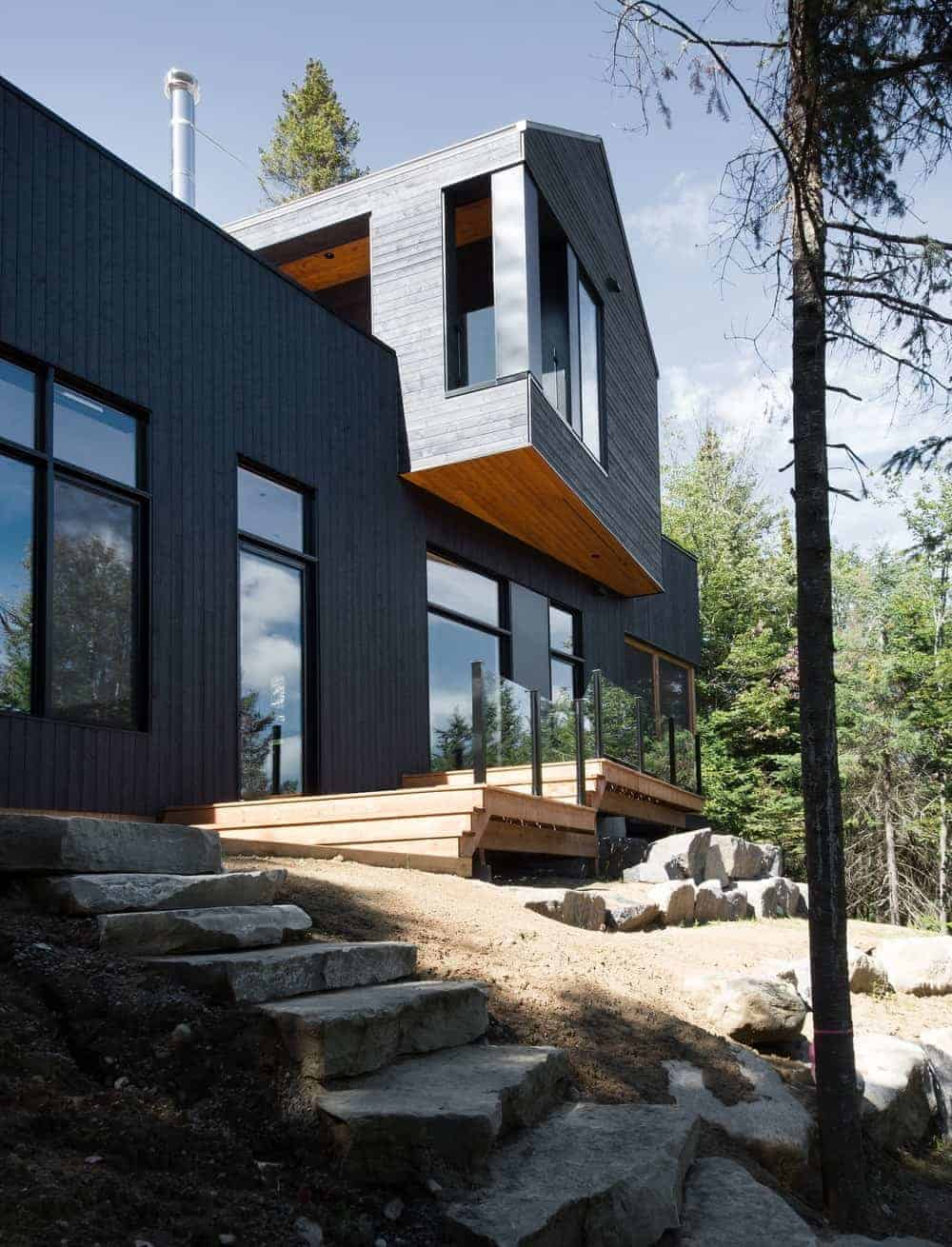A modern home featuring a wooden exterior painted in black.