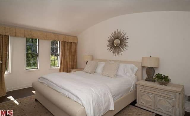 The Bedroom Features A Cream White Bed And Walls Along With Rug