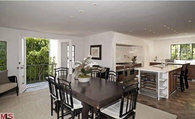 The kitchen features a dine-in table set with a classy rug.
