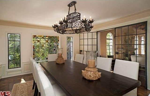 The dining room features an elegant table and chairs set lighted by a grand chandelier.
