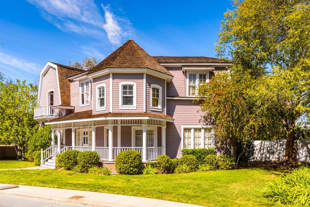 """This luxury house featured on the TV show """"Desperate Housewives"""" hit the spot with pink exterior siding for a feminine touch and visual texture while the brown roof blends with the green landscape."""